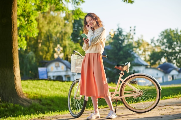 A picture of a girl with a bike in a park