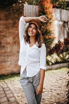 Picture of girl with short hair wearing brown cap, white blouse and linen trousers who raised her hand against space of brick building and bushes.