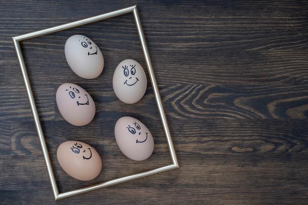 어두운 나무 벽 배경에 웃고 있는 황금색 프레임과 많은 재미있는 달걀이 클로즈업됩니다. 계란 가족 감정 얼굴 초상화입니다. 개념 재미있는 음식 프리미엄 사진