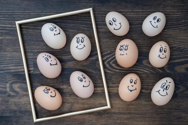 어두운 나무 벽 배경에 웃고 있는 황금색 프레임과 많은 재미있는 달걀이 클로즈업됩니다. 계란 가족 감정 얼굴 초상화입니다. 개념 재미있는 음식