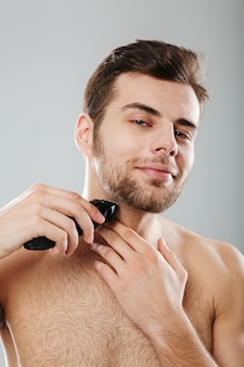 Picture of good-looking adult guy doing hygiene and health procedure with shaving his bristle using trimmer over grey wall