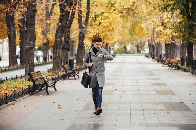 Picture of good-looking caucasian man in coat with bag strolling in city park, and looking at his watch
