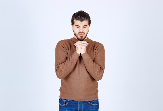 Picture of a good-looking man model holding hands together with closed eyes