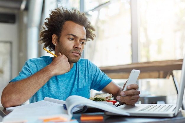 Picture of good-looking smart dark-skinned student in blue t-shirt working on course paper at college canteen, having sandwich and checking newsfeed via social networks on cell phone.