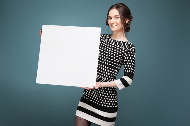 Picture of good looking woman in speckled clothes standing with big blank placard in hands