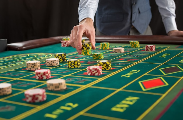 Picture of a green table and betting with chips. man hand over casino chips on roulette table. close up