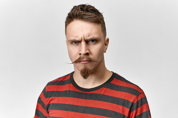 Picture of grumpy young male with messy hairstyle, waxed curly mustache and trimmed beard having dissatisfied severe facial expression, frowning eyebrows, disapproving inappropriate behavior