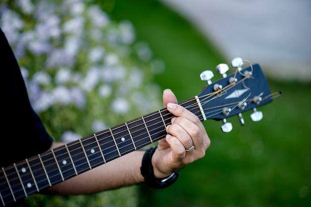 Picture of a guitarist, a young man playing a guitar while sitting in a natural garden,music concept