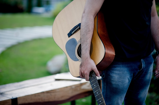 Picture of a guitarist, a young man playing a guitar while sitting in a natural garden