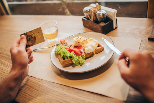 A picture of guy's hands holding gold card in left one. he is holding a knife with right one. there is a plate with tasty food on table. close up.