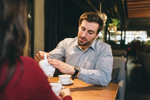 A picture of guy sitting at the table with his girlfriend and pouring some tea into the cup for them. he is listening to her very careful and accurate.