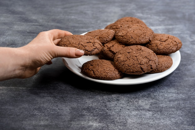 Picture of hands hold chocolate cookies  on plate
