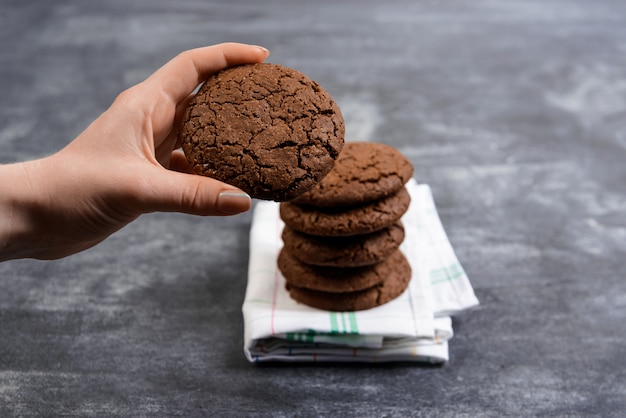 Picture of hands hold chocolate cookies over wooden surface