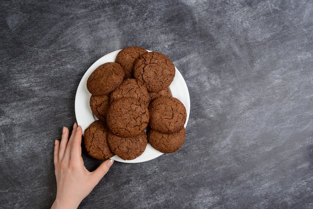 Picture of hands holding chocolate cookies over wooden surface