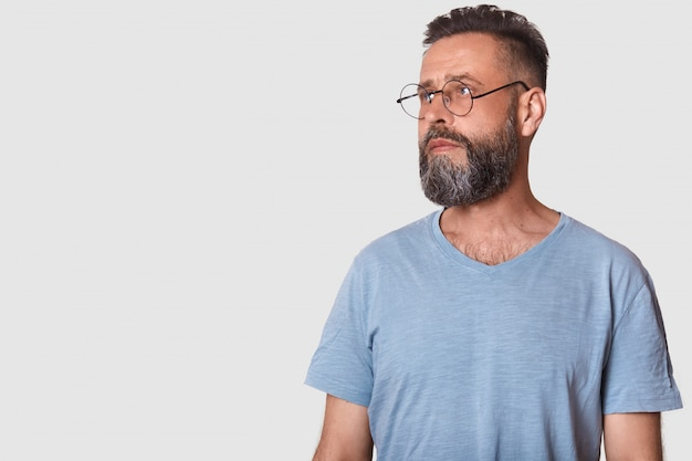 Picture of handsome bearded man wearing glasses and gray casual t shirt, posing isolated on white and looking aside. copy space for your advertisment or promotion text.