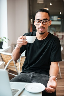 Picture of handsome businessman wearing glasses sitting near window and typing by laptop computer while drinking coffee