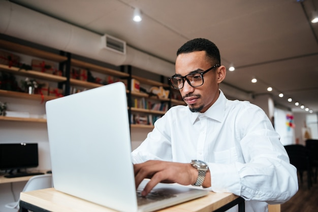 Picture of handsome businessman wearing glasses sitting at the table typing by laptop computer