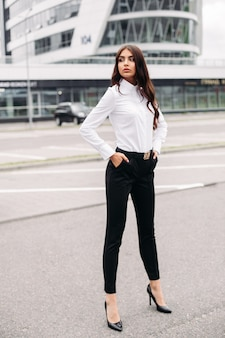 Picture of a handsome caucasian woman with long dark wavy hair in a white shirt, black pants and heels posing for the camera