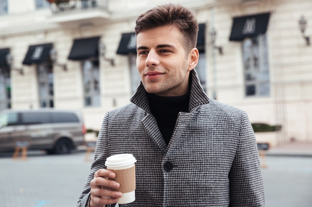 Picture of handsome man enjoying takeaway coffee from paper cup, while walking down empty street