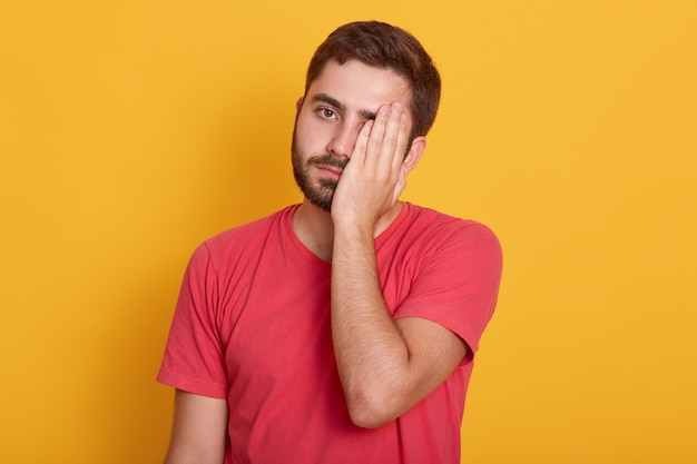 Picture of handsome man wearing casual red t shirt, standing with sad expression, covering half of his face with hand, looks tired