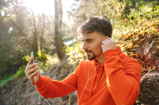 Picture of handsome young sports fitness man runner outdoors in park listening music with earphones using mobile phone take a selfie talking.
