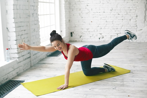 Picture of happy charming young female with hair bun doing physical training in light room, performing plank, raising opposite leg and arm, preparing body for summer. people and active lifestyle