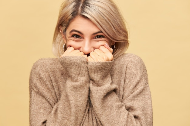 L'immagine di una giovane donna europea felice e gioiosa non può nascondere le sue emozioni estatiche, essere di buon umore, sopraffatto da ottime notizie positive, nascondere la bocca dietro le mani, indossare un maglione accogliente a maniche lunghe
