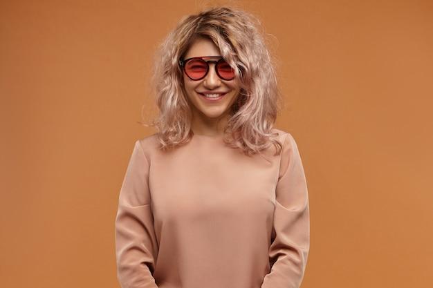 Foto di felice giovane femmina positiva che indossa abiti e accessori alla moda che hanno una buona giornata