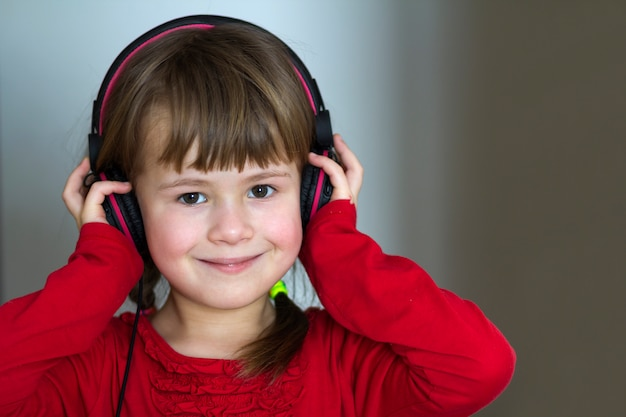 Picture of happy pretty child little girl with big headphones at home. joyful child girl listening to music on gray blurred  home, technology and music concept.