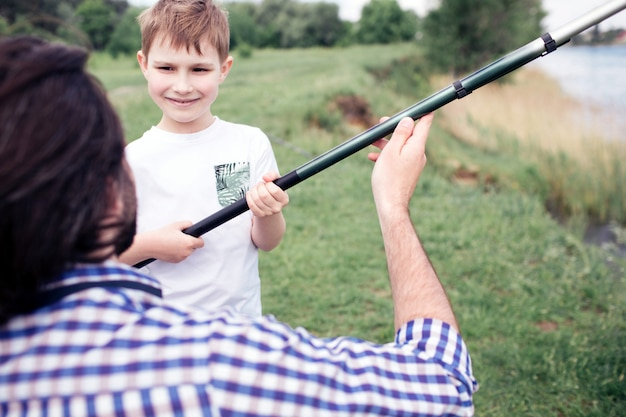 A picture of happy son standing in front of his dad and holding long fish-rod. guy is holding it a bit. they are spending time together.