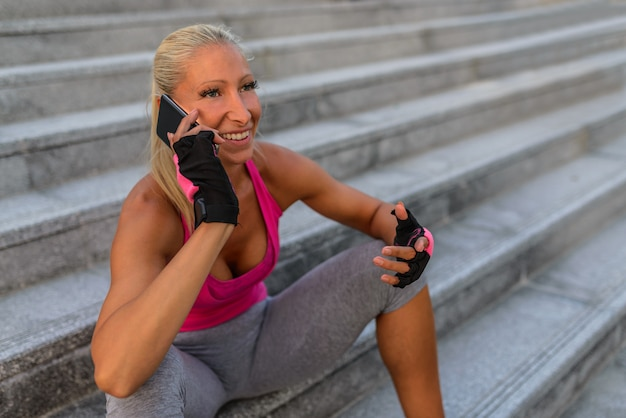 Picture of a happy sport woman using mobile phone on concrete stairs