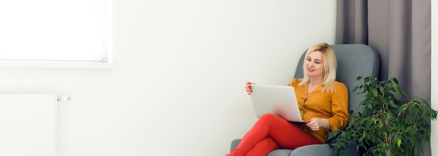 Picture of happy woman using laptop at home