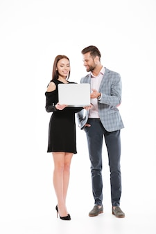 Picture of happy young loving couple standing isolated. looking aside while using laptop computer.