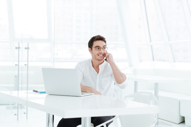 Picture of happy young man dressed in white shirt using laptop computer while talking by phone. look aside.