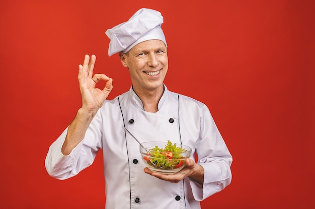 Picture of happy young senior chief cook in uniform standing isolated over red wall background, holding salad.
