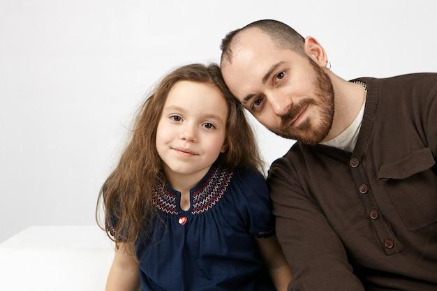 Foto di felice giovane padre single con la barba alla moda che sorride alla macchina fotografica con il suo bambino femminile affascinante, che propone contro il fondo bianco della parete dello studio con copyspace