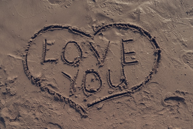 Picture of heart with 'love you' sign on sand
