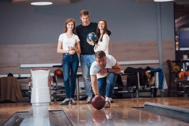 Картина в движении. молодые веселые друзья веселятся в боулинг-клубе на выходных