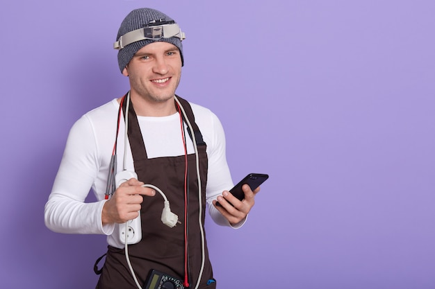 Picture of joyful electronic engineer holding smartphone and plug, having cords and electronic equipment, tools on neck, smiling sincerely