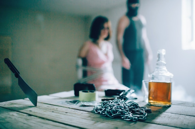 A picture of killer in mask standing besudes his victim. she is tied with ropes to the chair. there are chains, bootle of alcohol and knife on the table.