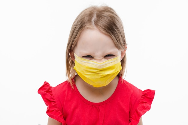 Picture of little beautiful caucasian girl with long fair hair in red dress with yellow medical mask on her face is angry