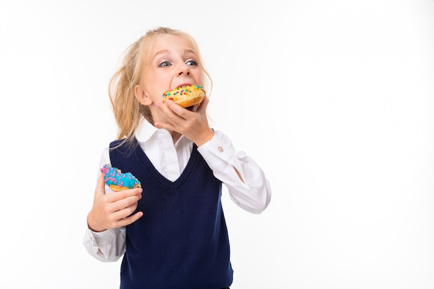 Picture of a little girl with blonde hair eats donuts