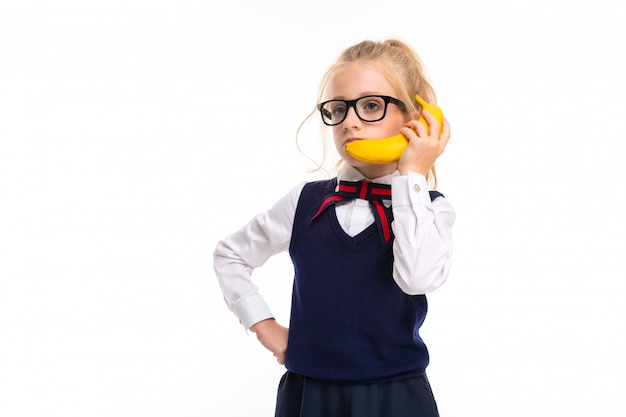Picture of a little girl with blonde hair talking on banana