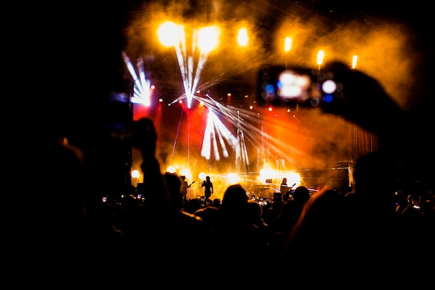 Picture of a lot of people enjoying night perfomance, large unrecognizable crowd dancing with raised up hands and mobile phones on concert. nightlife