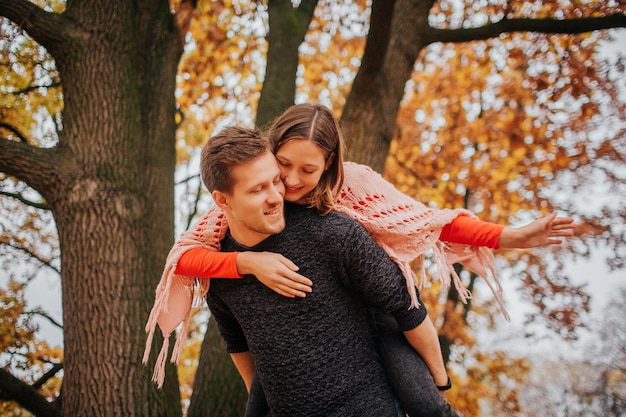 Picture of lovely couple spending time in park. she embrace him. he holds her on back. autumn in outside.