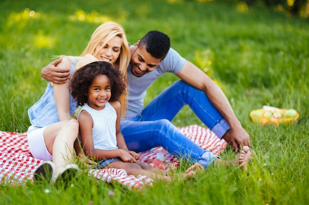 Picture of lovely couple with their daughter having picnic in nature
