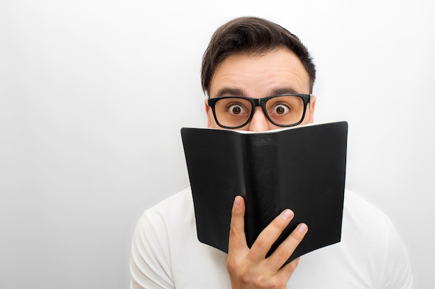 Picture of male brunette looking. he holds black book in hands. he weas glasses. young man is excited.