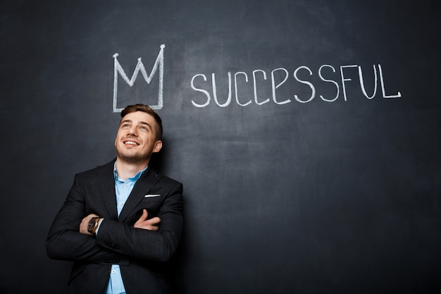 Picture of man over blackboard with crown and text successful