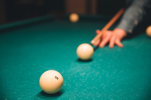 Picture of man's hand holding billiard cue and aiming to breal ball. he plays inside on bed of table.