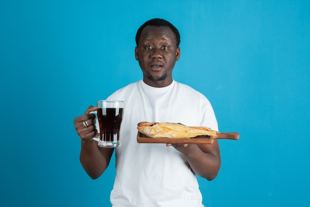 Picture of a man in white t-shirt holding dried fish with a glass mug of wine against blue wall
